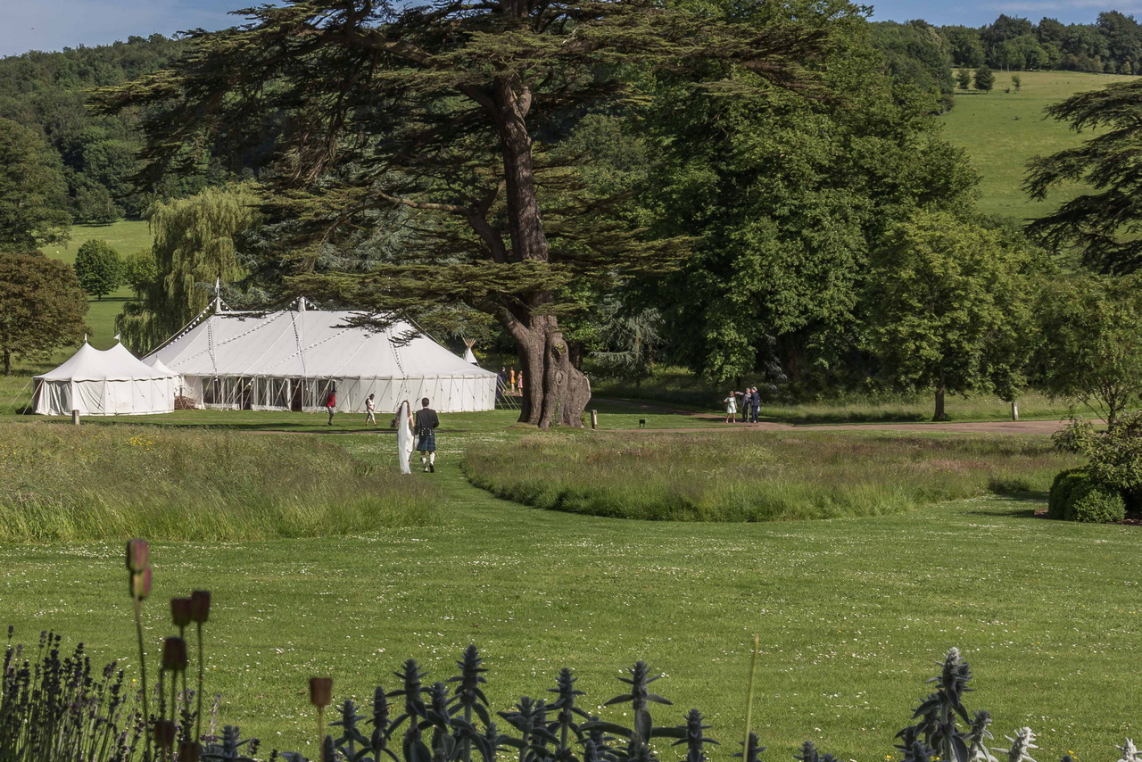 Bride and Groom walk towards their marquee in West Dean Gardens. Credit Steve Tattersall